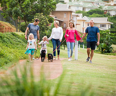 Retirement Villages provide safety. Family walking dogs on gated, secure estate on Mount Edgecombe Retirement Village